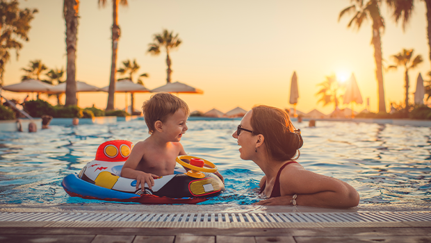 mother and child in a pool with palm trees and a sunset in the background