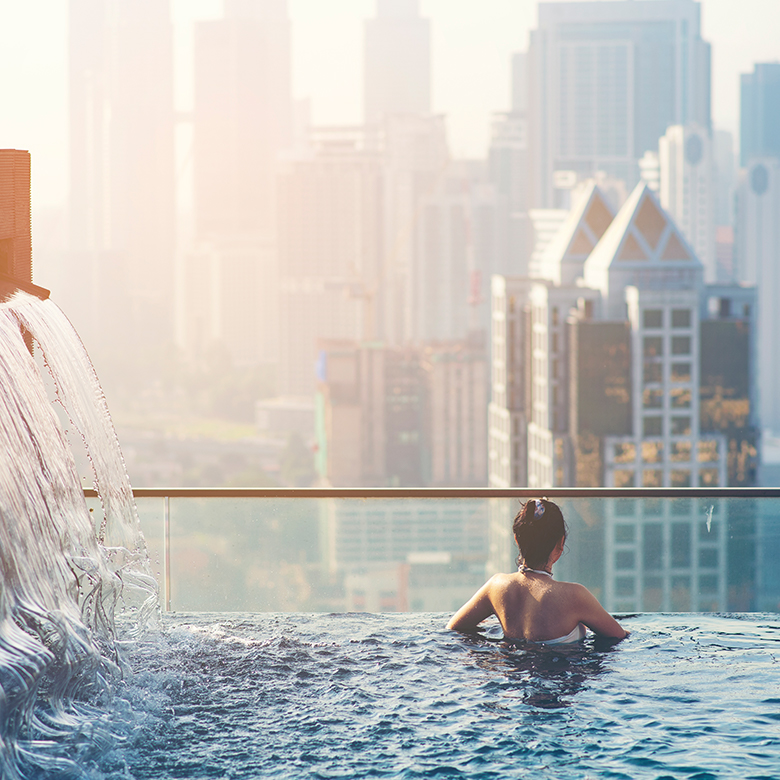 Woman in an infinity pool overlooking the city