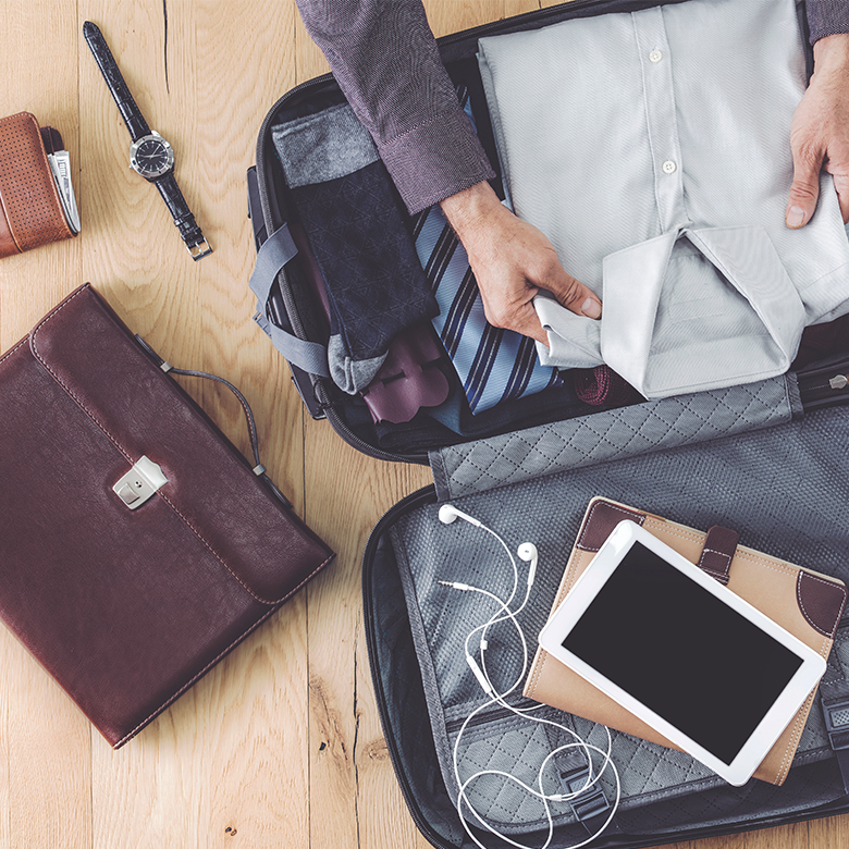 Business traveller packing for a business trip