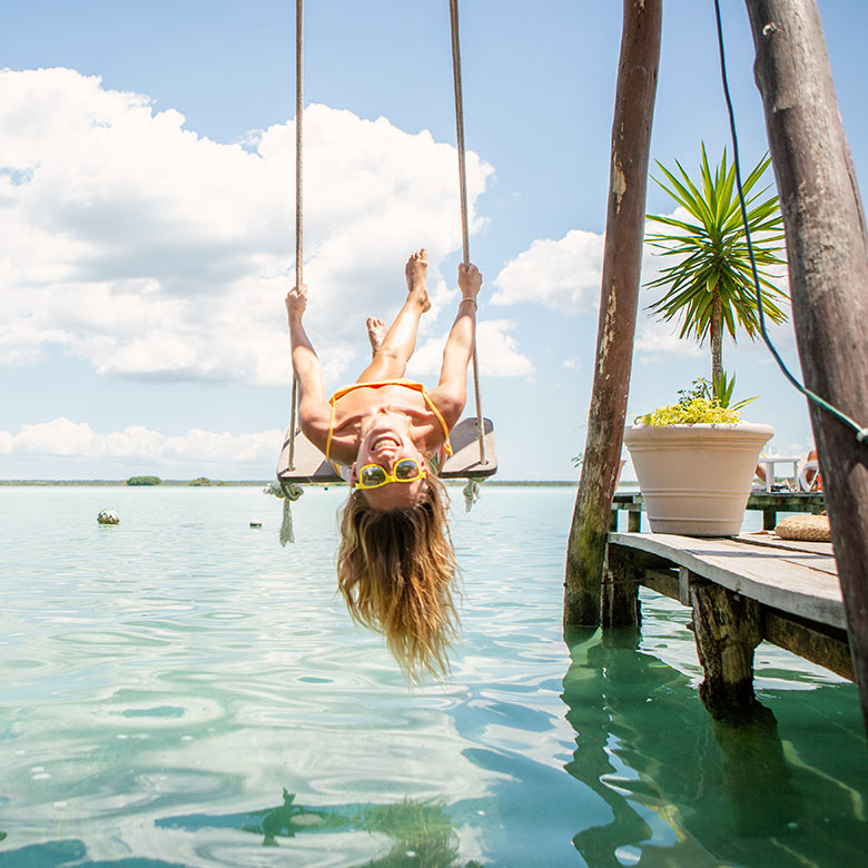 traveller plays on overwater swing set in cancun