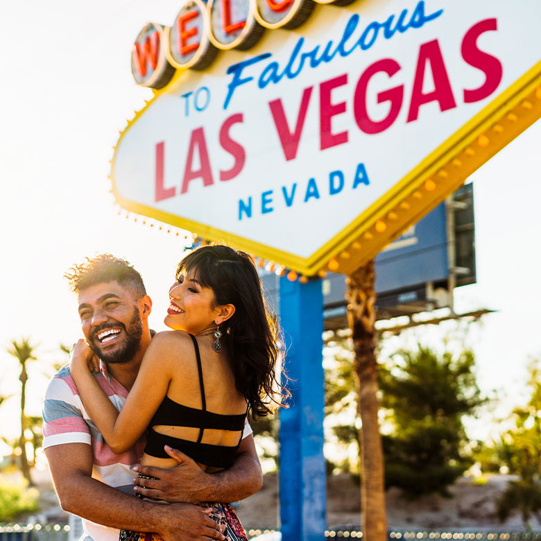 two travelling friends embrace in front of welcome to las vegas sign
