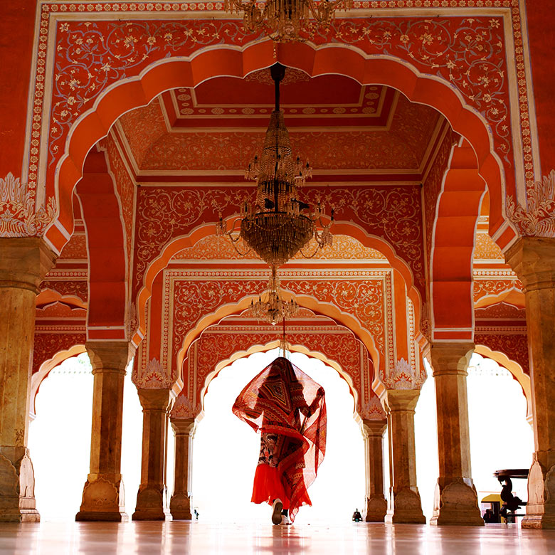 Woman standing under an ornate red archway in Rajasthan, India