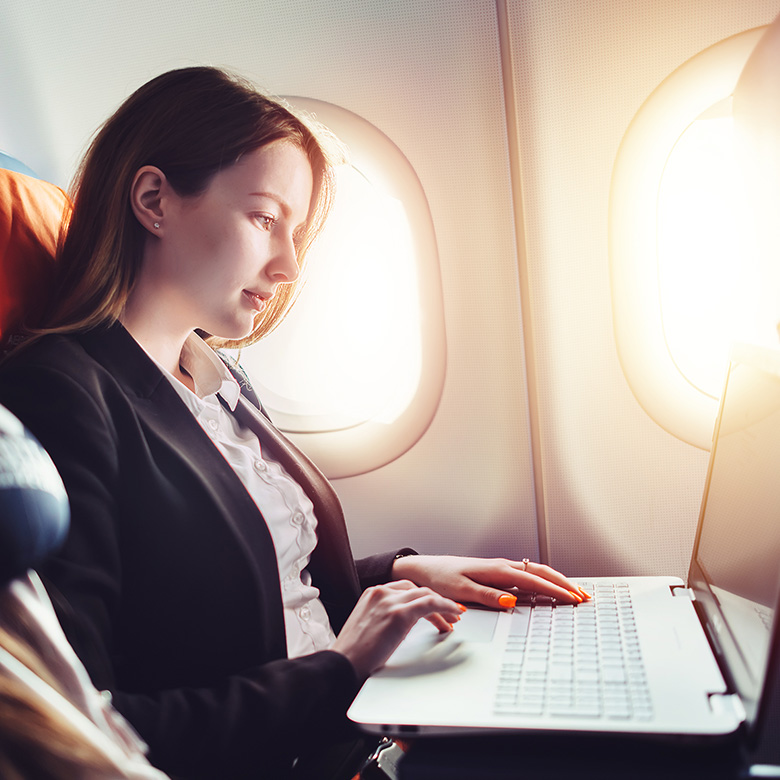 business woman works on laptop in plane business class seat