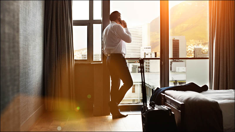 a business traveller talks on the phone while looking out of hotel window
