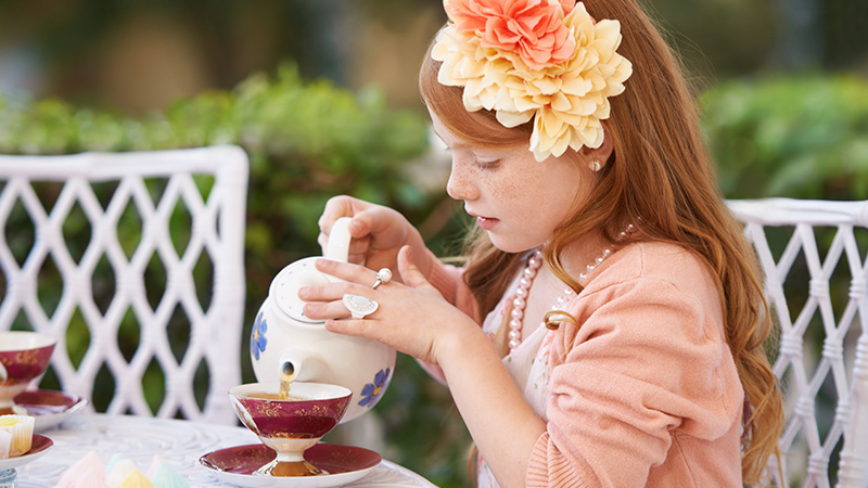 young girl wearing fascinator pours a cup of tea outside