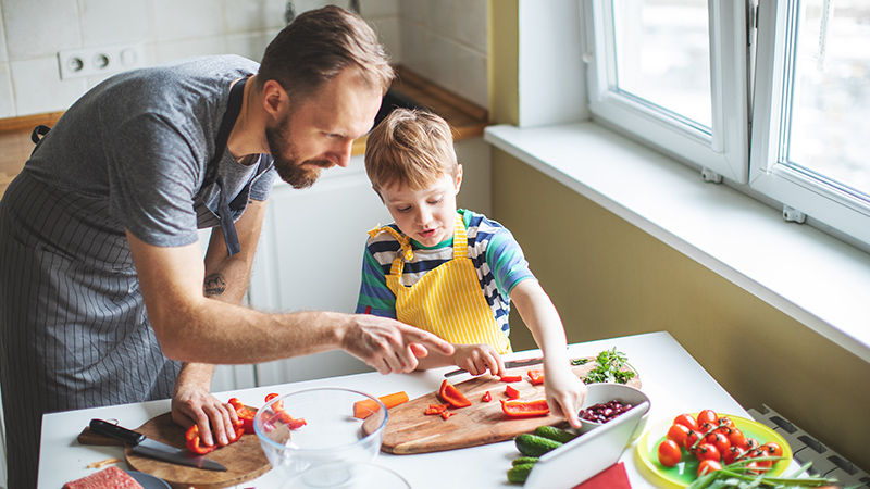 father and son prepare mothers day meal