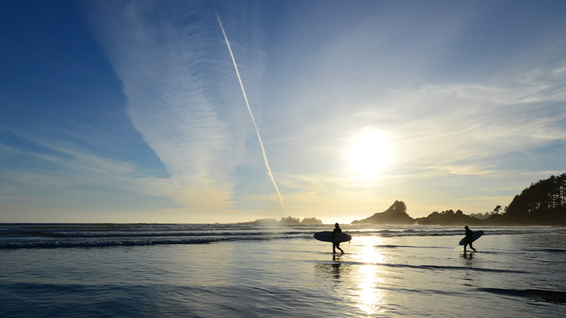 travellers walk along tofino beach with surfboards