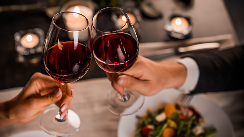 two travellers toast glasses full of red wine at jw marriott los cabos
