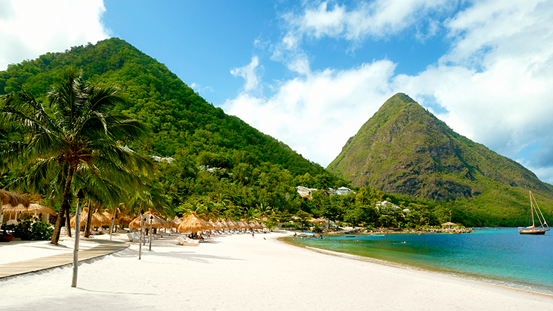 piton mountains behind white sand beach at sugar beach viceroy hotel