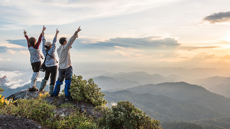 three travellers raise the arms at the summit of a mountain