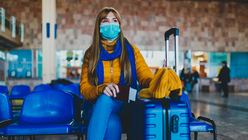 woman wearing face mask waits for flight