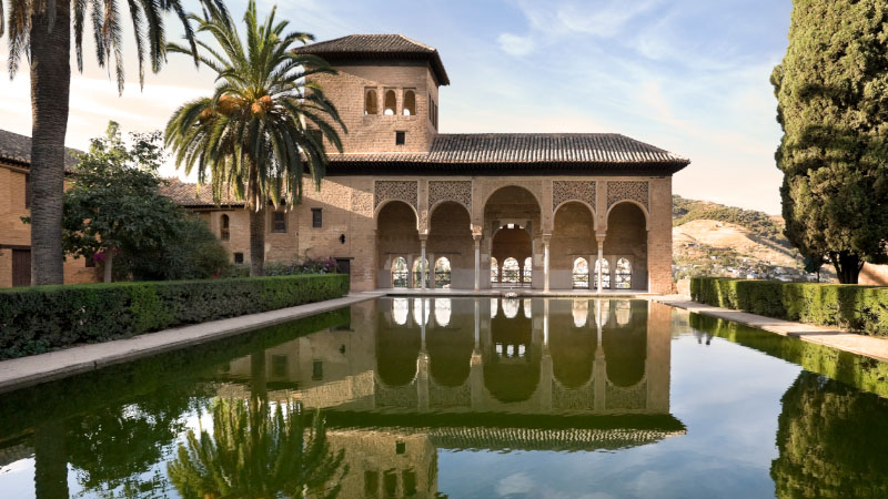 a calm pool reflects a colonial building in granada