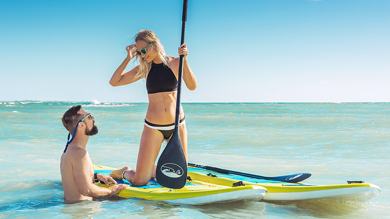 two travellers smile at each other while stand up paddle boarding at andaz mayakoba