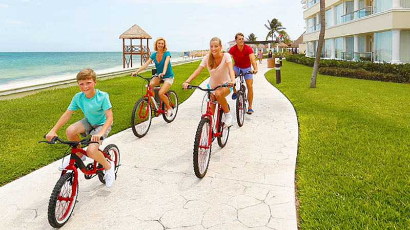 family of four bike around grand at moon palace resort in mexico