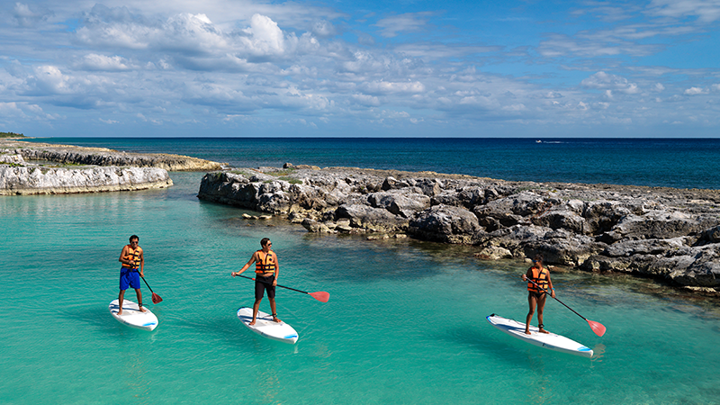 three friends stand up paddle board at hard rock hotel riviera maya