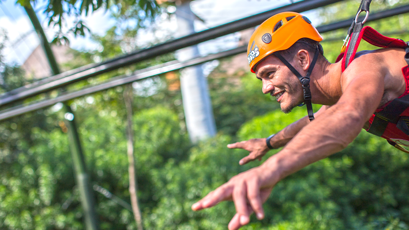 young man zip lines at xcaret park