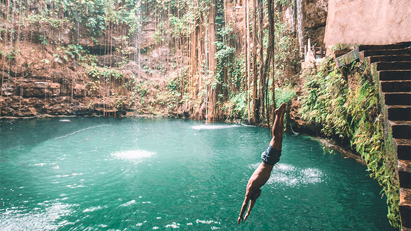 man dives into cenote in mexico