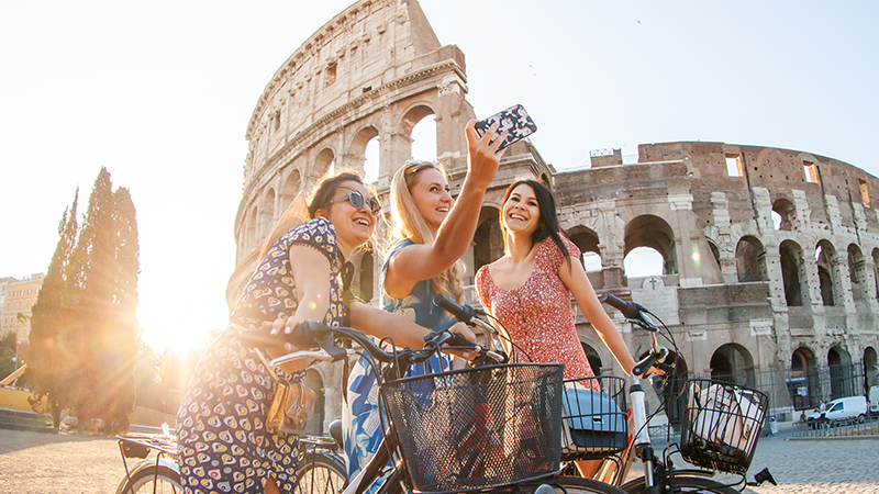 three women on bicycles take a selfie in front of roman colosseum