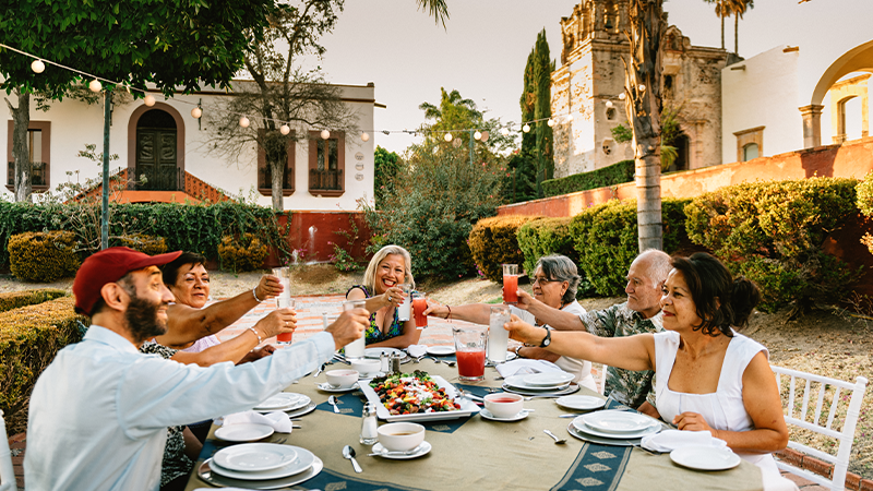 group of friends toast over an outdoor meal in mexico