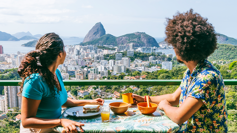 man and woman enjoy meal on balcony in rio brazil