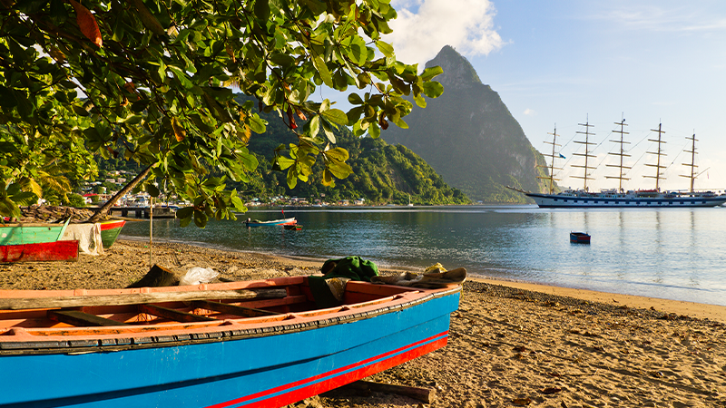 colourful boats docked on a beach with piton mountains in view