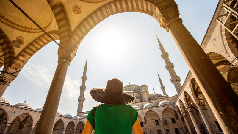 woman looks up at spires of blue mosque in turkey