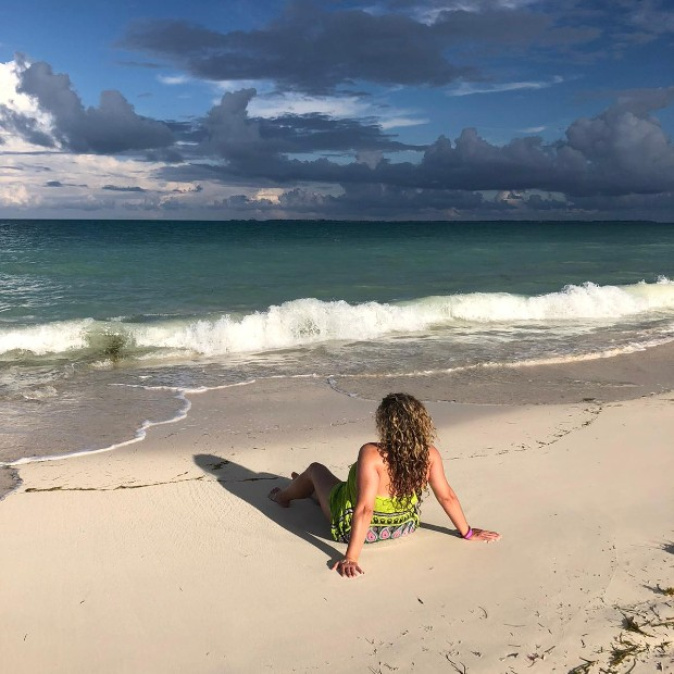 a woman in a bright green sun dress leans back on the sand at a beach in riviera maya
