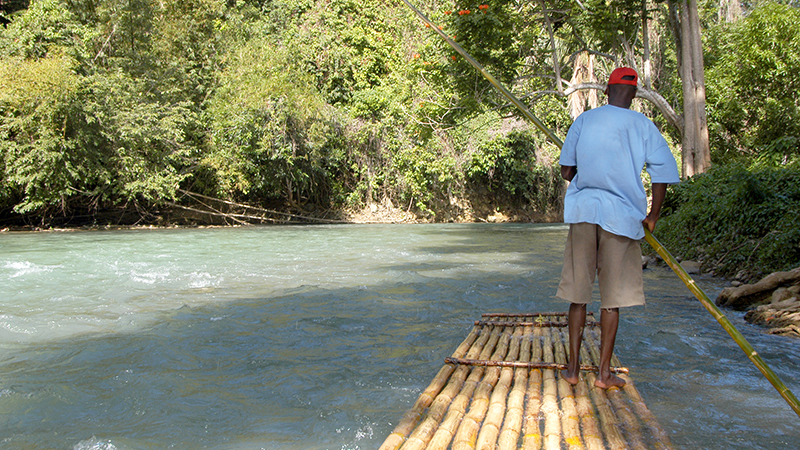 man steers wooden raft floating on martha brae river