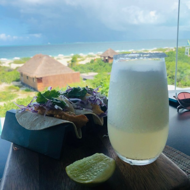 a cold cocktail and taco lunch sit on a table overlooking the ocean in riviera maya