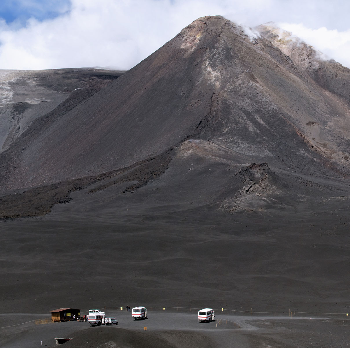 a distant caravan of cars gather at the base of mount etna in sicily italy