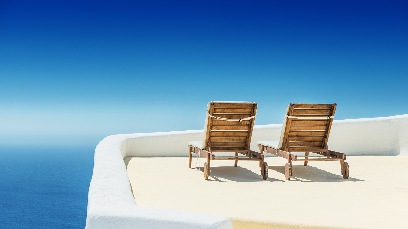 two lounge chairs side by side on a balcony in santorini
